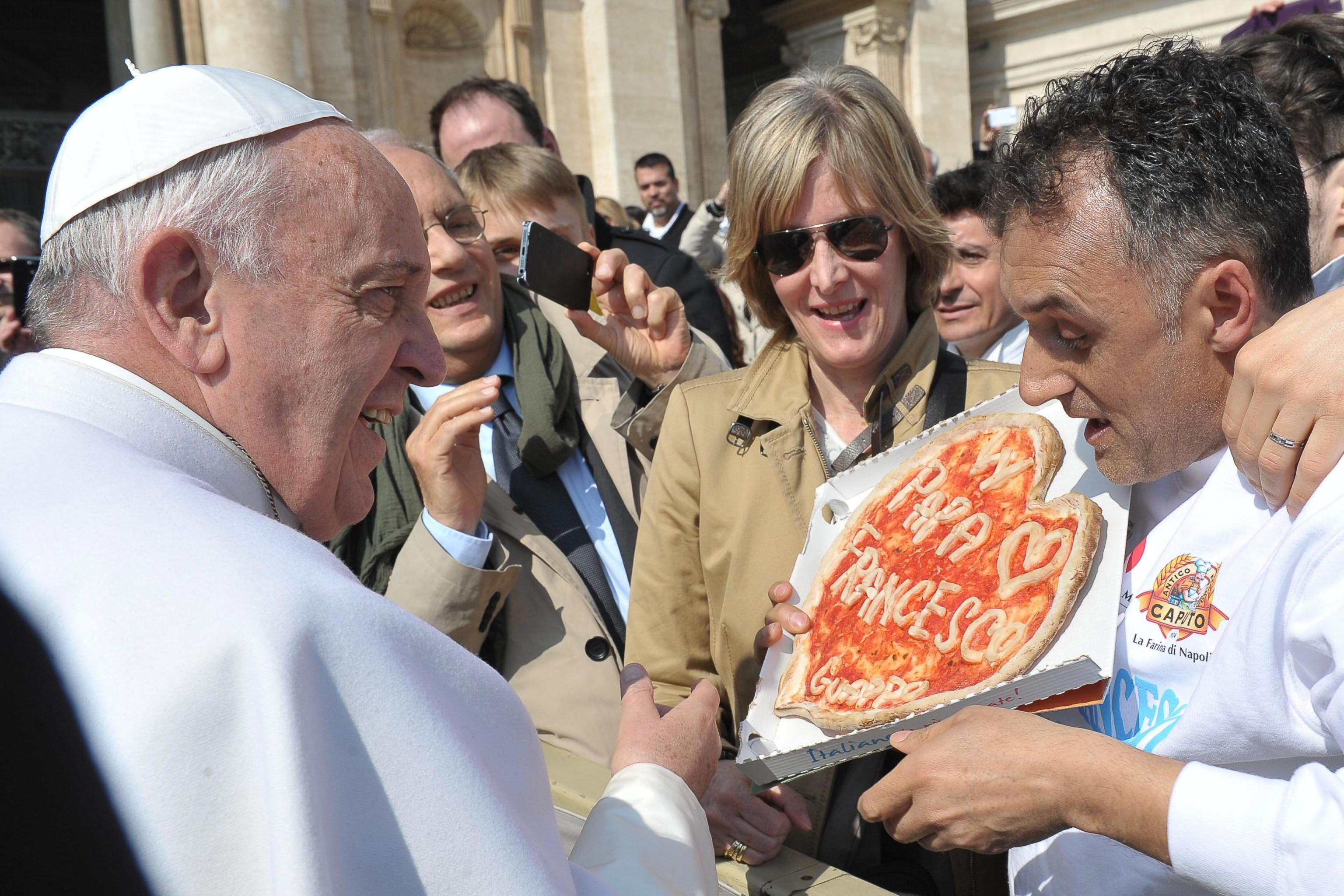 epa04657751 A handout photograph made available by the L'Osservatore Romano - Press Office showing Pope Francis receiving a gift of a special pizza during his weekly general audience in Saint Peter's Square, Vatican City, 11 March 2015.      +++ANSA PROVIDES ACCESS TO THIS HANDOUT PHOTO TO BE USED SOLELY TO ILLUSTRATE NEWS REPORTING OR COMMENTARY ON THE FACTS OR EVENTS DEPICTED IN THIS IMAGE; NO ARCHIVING; NO LICENSING+++  EPA/L'OSSERVATORE ROMANO / HANDOUT  HANDOUT EDITORIAL USE ONLY/NO SALES/NO ARCHIVES